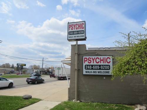 poem is on cinderblock wall beneath Psychic sign